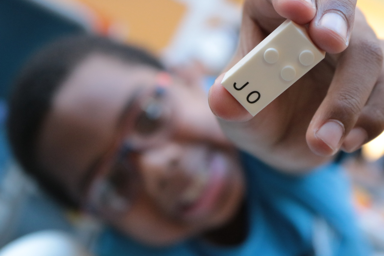 Em primeiro plano a mão de um menino segura uma peça branca com pontos em alto relevo, que faz parte do projeto de educação inclusiva da Lego. Embaixo dos pontos se lê as letras J e O. Ao fundo, desfocado está o rosto do garoto, que usa óculos e sorri.