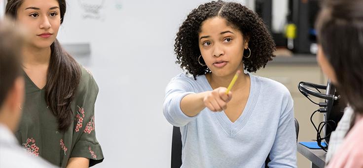 Imagem mostra uma jovem com uma mão levantada, na qual segura um lápis, participando de discussão em aula. Mudança climática é um tema que pode mobilizar jovens em sala de aula.