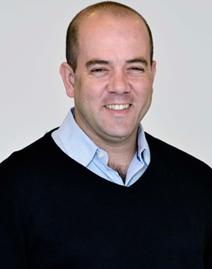 Retrato mostra Americo Mattar usando suéter e camisa e sorrindo para a foto. Na matéria, o diretor-presidente da Fundação Telefônica Vivo fala sobre o Desafio Inova Escola.