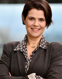 Retrato mostra Mila Gonçalves vestindo camisa e terno e sorrindo para a foto. Na matéria, a gerente de programas sociais da Fundação Telefônica Vivo fala sobre o Desafio Inova Escola.
