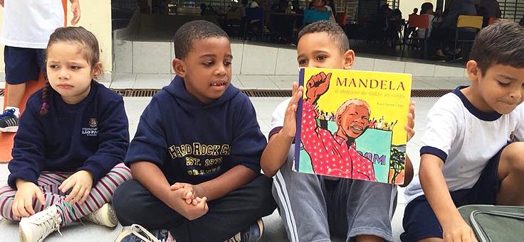 Quatro alunos da EMEI Nelson Mandela estão sentados de pernas cruzadas no chão, um deles segurando um cartaz com Mandela desenhado com o punho direito cerrado e levantado.