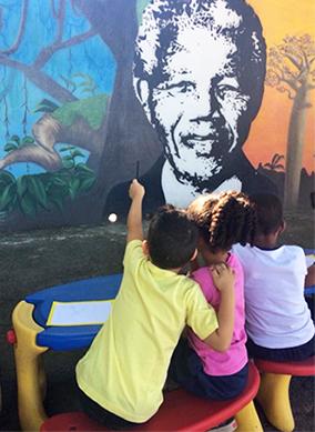 Três alunos estão sentados em frente a muro da EMEI Nelson Mandela, onde está desenhado o rosto de Madiba com árvores típicas da savana africana ao fundo.