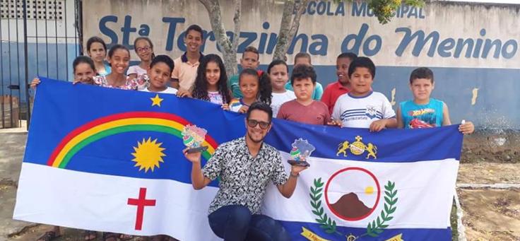 Educador Isaías Silva está agachado, segurando troféus do Prêmio Professores do Brasil. Atrás dele está um grupo de alunos, mostrando as bandeiras de Pernambuco e de Vitória de Santo Antão.