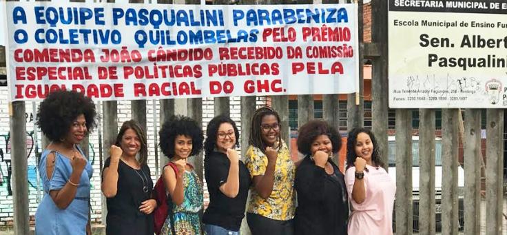 Mulheres do coletivo feminista Quilombelas estão posando com os punhos levantados indicando força. Acima delas há uma faixa de homenagem por um prêmio conquistado.