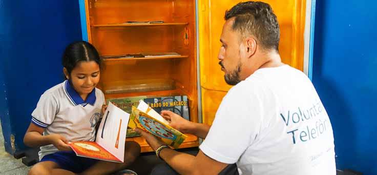 Colaborador e aluna estão segurando livros e sentados lado a lado na Escola Municipal de Ensino Fundamental Frei Fernando, que recebeu o programa de voluntariado Vacaciones Solidárias.