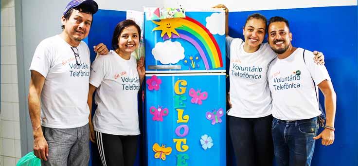Colaboradores posam ao lado de quadro com arco-íris desenhado na Escola Municipal de Ensino Fundamental Frei Fernando, que recebeu o programa de voluntariado Vacaciones Solidárias.