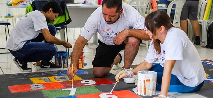 Colaboradores usam pincéis para pintar amarelinha no chão da Escola Municipal de Ensino Fundamental Frei Fernando, que recebeu o programa de voluntariado Vacaciones Solidárias.