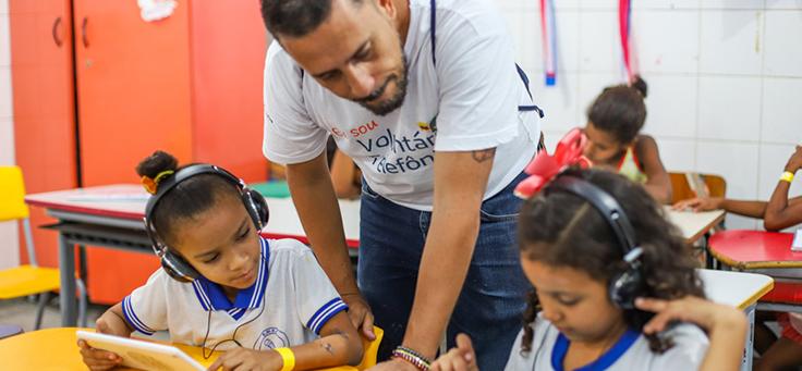 Colaborador do programa de voluntariado Vacaciones Solidárias está observando duas alunas da Escola Municipal de Ensino Fundamental Frei Fernando que estão sentadas na carteira escrevendo.