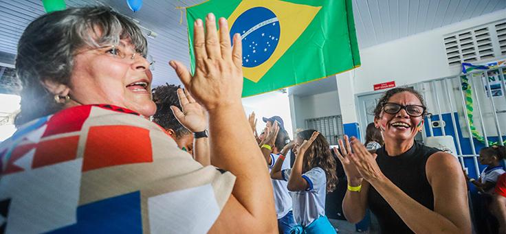 Duas colaboradoras do programa de voluntariado Vacaciones Solidárias batem palma, com bandeira do Brasil ao fundo.