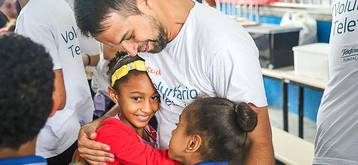 Colaborador está abraçando duas alunas da Escola Municipal de Ensino Fundamental Frei Fernando, que recebeu o programa de voluntariado Vacaciones Solidárias.