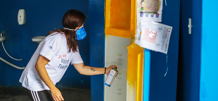 Colaboradora está pintando porta com spray amarelo na Escola Municipal de Ensino Fundamental Frei Fernando, que recebeu o programa de voluntariado Vacaciones Solidárias.