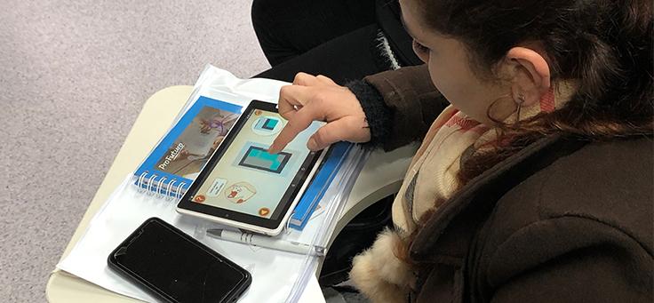 Imagem mostra uma criança sentada mexendo em um tablet