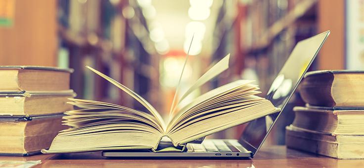 Livro está aberto em cima de teclado de computador e, ao fundo, aparecem desfocadas estantes de uma biblioteca. A imagem ilustra a história da educadora Angélica Tinaut, que criou um site e tem 69 anos de carreira.