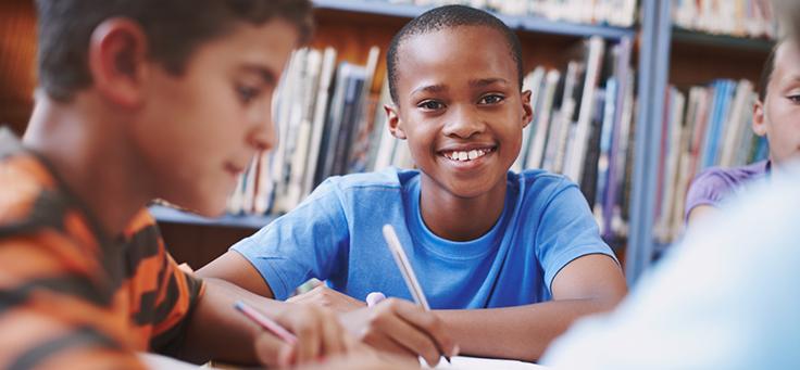Menino está sentado em meio a livros, sorrindo e segurando um lápis para ilustrar pauta sobre formação de educadores para melhorar a alfabetização.