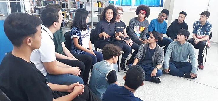 Imagem mostra grupo de alunos sentados em roda dentro de uma biblioteca