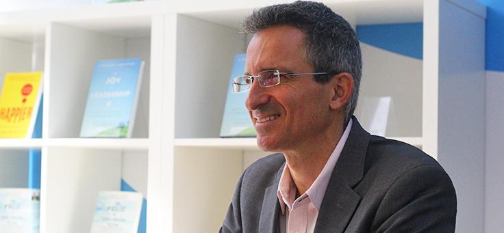 Tal Ben-Shahar, CEO da Happiness Studies Academy e professor da Universidade de Harvard, está sentado em frete a uma estante com livros. No enlightED, ele relacionou o avanço da tecnologia à felicidade.