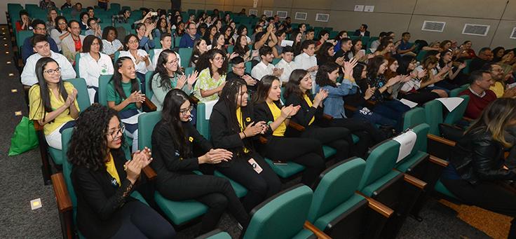 Pessoas estão sentadas em plateia de teatro aplaudindo participação de grupos durante o Demoday.