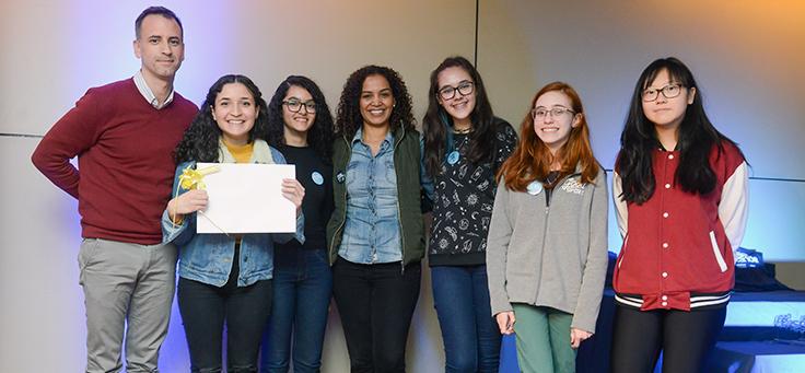 Grupo de estudantes posa ao lado de professor com uma delas segurando um quadro branco, durante o Demoday.