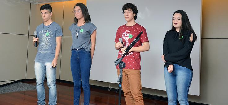 Grupo de quatro estudantes se apresenta durante o Demoday. Dois deles estão com o microfone nas mãos