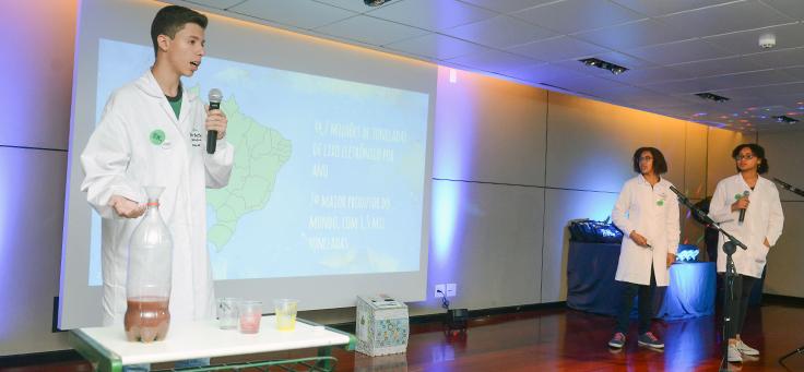 Três estudantes apresentam seu projeto durante o Demoday. Eles usam jalecos brancos e mostram uma experiência. Atrás deles há uma apresentação com o mapa do Brasil.