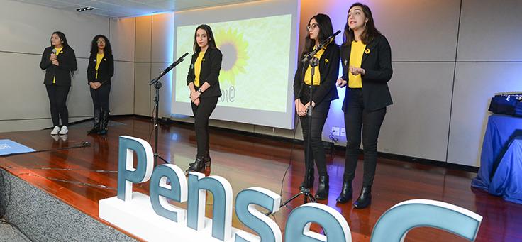 Grupo de estudantes se apresenta no palco. Elas usam roupas pretas e amarelas. Ao fundo se vê um girassol. Na frente delas está o logo do programa Pense Grande.