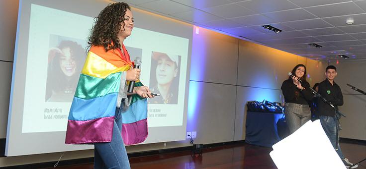 Imagem mostra jovem enrolada em bandeira LGBT. Dois colegas a observam no palco