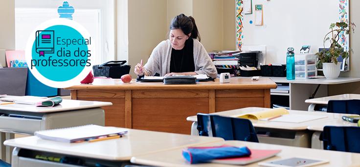 Professora está sentada em sua mesa, rodeada por carteiras vazias em sala de aula. Pesquisa mostra que solidão é um sentimento comum entre educadores.