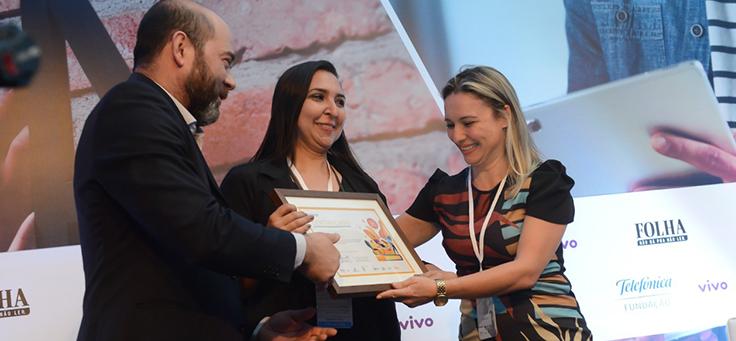 Imagem mostra participantes do grupo Arteduca recebendo prêmio de Americo Mattar, Diretor-Presidente da Fundação Telefônica Vivo