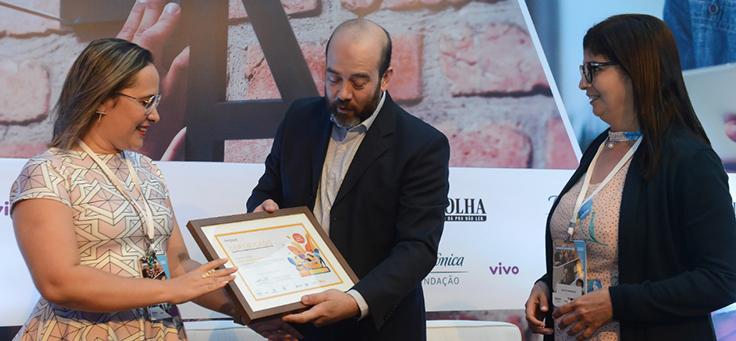 Imagem mostra participantes do grupo Santa Terezinha recebendo prêmio de Americo Mattar, Diretor-Presidente da Fundação Telefônica Vivo