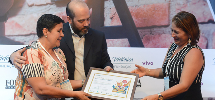 Imagem mostra participantes do grupo Nenhum a Menos recebendo prêmio de Americo Mattar, Diretor-Presidente da Fundação Telefônica Vivo