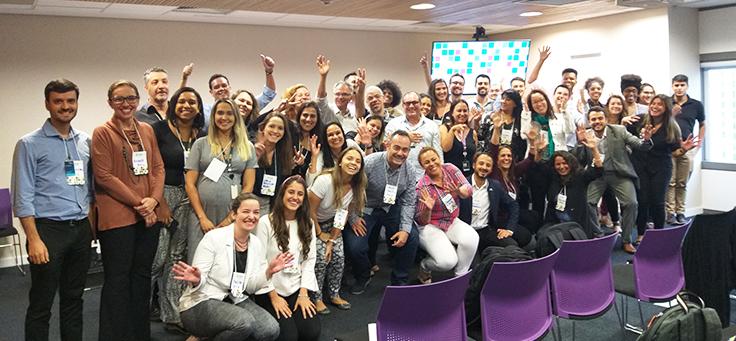 Grupo de 50 pessoas que participaram do evento Prata da Casa, que destacou ações pela inclusão do Programa de Voluntariado da Fundação Telefônica Vivo, estão sorrindo e acenando para a foto.