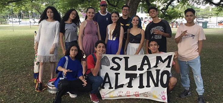 Alunos da Escola Municipal Altino Arantes posam para foto em grupo segurando uma faixa com os dizeres: Slam Altino