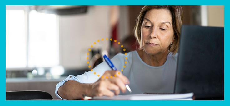 Imagem mostra mulher estudando em frente ao computador. Ela faz anotações à mão.