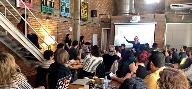 Imagem mostra pessoas em uma sala, durante formação do projeto EducaMídia, sentados em grupos em volta de mesas redondas, olhando para a frente, onde se vê uma projeção na parede e uma mulher em pé.