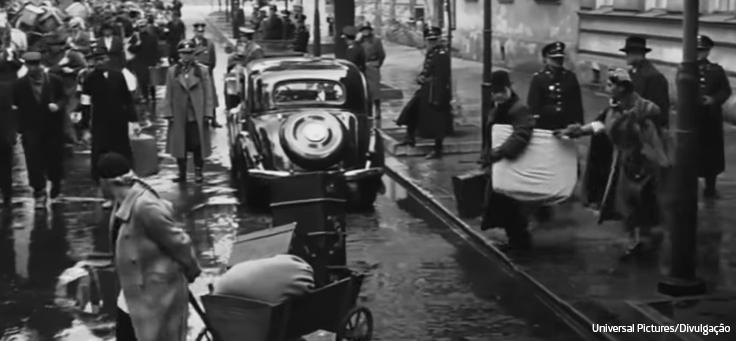 Imagem em preto e branco mostra carros antigos e pessoas carregando pertences nas ruas em cena de A Lista de Schindler, que está em lista de filmes que debatem direitos humanos.