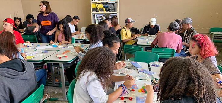 Imagem mostra alunos sentados em mesas coletivas desenvolvendo projetos para a Hora do Código