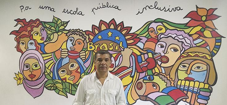Imagem mostra um homem em frente a uma parede desenhada