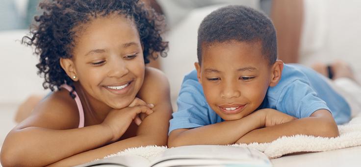 Imagem mostra duas crianças deitadas olhando para um livro