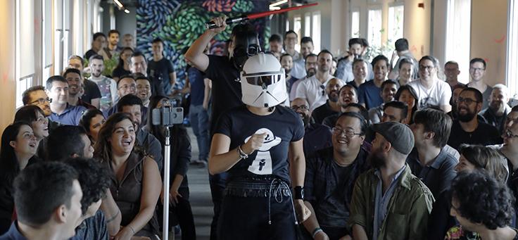 Imagem mostra duas pessoas caminhando de máscaras no meio de uma sala onde há diversas pessoas sentadas