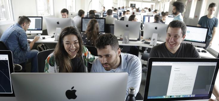 Imagem mostra um laboratório com diversos MAcbooks e pessoas