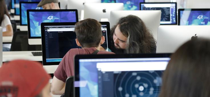 Na imagem um homem auxilia um garoto mais novo a mexer no computador