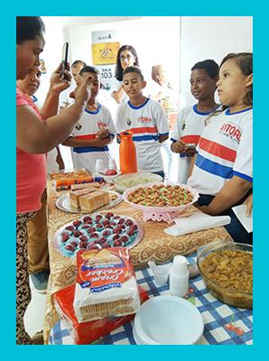 Imagem mostra alunos em volta de uma mesa com alimentos durante atividade de projeto sobre alimentação saudável.