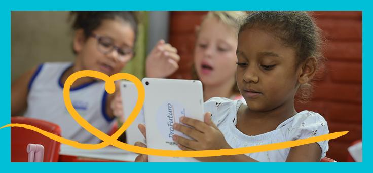 Imagem mostra uma criança em destaque olhando para um tablet onde se lê ProFuturo na parte de trás. Ao fundo é possível ver mais duas crianças.