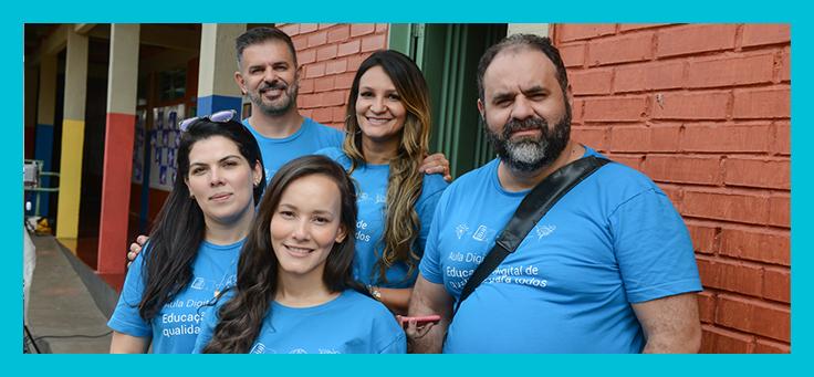 Um grupo de pessoas posa para foto usando a camiseta do projeto Aula Digital na Escola Municipal Benedito Soares de Castro