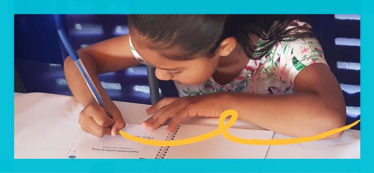 Na foto, uma menina aparece autografando o livro escrito por ela durante a Manhã de Autógrafos da escola