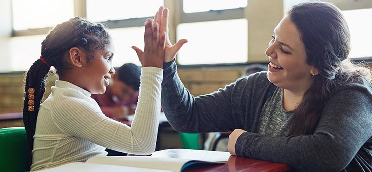 A imagem mostra uma criança com a mão levantada juntando a palma da mão com a de uma mulher