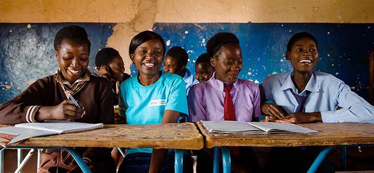 Imagem mostra um grupo de crianças sorrindo sentadas em uma sala atrás de mesas de madeira