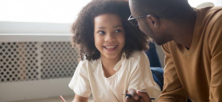 Imagem mostra uma criança sorrindo olhando seu pai