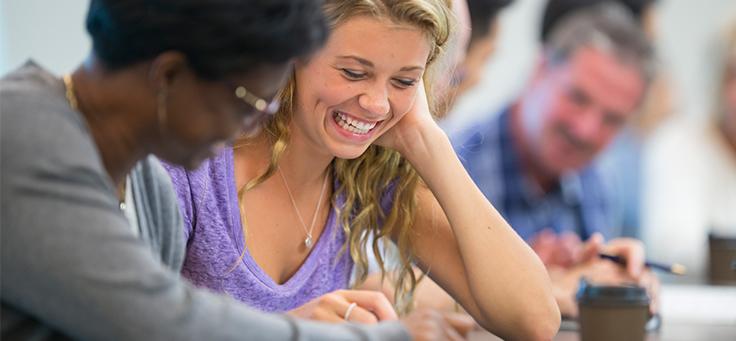 imagem mostra duas mulheres sentadas sorrindo