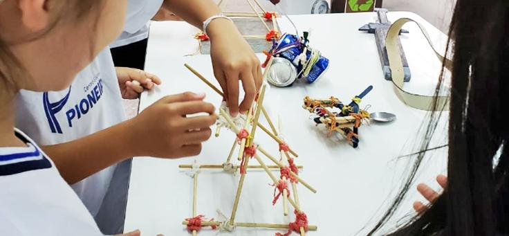 Imagem mostra uma mão em destaque montando uma estrutura de palitos
